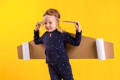 Freedom, girl playing to be airplane pilot, funny little girl with aviator cap and glasses, carries wings made of brown. Cardboard as an airplane. Studio Royalty Free Stock Images