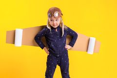 Freedom, girl playing to be airplane pilot, funny little girl with aviator cap and glasses, carries wings made of brown Stock Image