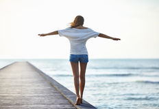 Freedom girl walking on pier. Freedom girl walking on the pier Royalty Free Stock Image