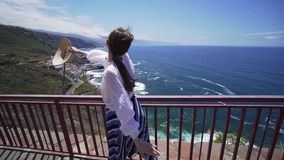 Freedom and happiness concept - joyful woman repenting her hands on the background of the Atlantic Ocean and the coast. Of Tenerife. Model Girl on a Windy Day stock footage