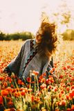 Happy beautiful woman relaxing in poppy flower field. Freedom happy beautiful young woman relaxing in poppy flower field on sunny summer day, her hair fly-away royalty free stock photography