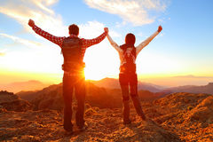 Freedom - Happy couple cheering and celebrating. Hiking men and women raising arms excited in celebration outdoors. Hikers at sunset in mountain enjoying stock photo