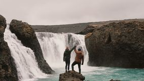 Freedom: happy couple after hiking standing near the waterfall in Iceland and raising hands together. Traveling man and woman enjoying beautiful landscape stock video