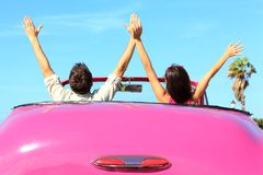Freedom - happy free couple in car. Driving in pink vintage retro car cheering joyful wih arms raised. Friends going on road trip travel on summer day under sun royalty free stock photography