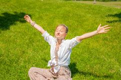 Freedom and happy moment. Beautiful woman with raising up her hands is sitting on grass, enjoy sunny day stock images