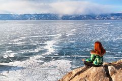 Freedom happy redhead woman sitting in meditation enjoying view of a frozen lake Baikal surface. Winter tourism concept Royalty Free Stock Photos