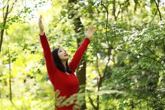 Freedom happy woman feeling alive and free in nature breathing clean and fresh air. Carefree young adult dancing in forest or park showing happiness with arms Stock Images