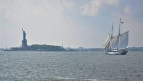 Lady Liberty in New York Harbor. Statue of Liberty in NY Harbor.  Sailboat is a two-masted ketch flying an American Flag.   Photo was shot in early pm, slight Stock Photos