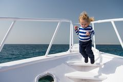 Freedom and joy. Adventure boy sailor travelling sea. Child cute sailor carefree jump yacht bow. Boy adorable sailor. Striped shirt yacht travel around world royalty free stock images