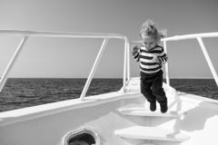 Freedom and joy. Adventure boy sailor travelling sea. Child cute sailor carefree jump yacht bow. Boy adorable sailor. Striped shirt yacht travel around world royalty free stock image