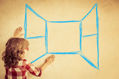 Freedom. Kid looking out of the drawn open window on grunge wall. Freedom concept Royalty Free Stock Image