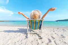 Freedom life of Girl at beach. Freedom life of Girl with Hat on chair beach relaxing at very beautiful beach and blue sky Royalty Free Stock Photo