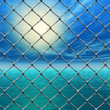 Freedom - Link fence over sunny sky and sea Stock Photos