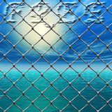 Freedom - Link fence over sunny sky and sea Royalty Free Stock Photography