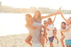 Freedom, love, friendship, summer mood. Happy young boyfriends p. Iggybacking their girlfriends at the seaside, having fun, so cheerful and carefree royalty free stock image