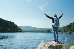 Freedom. Man with backpack raising hands while standing by lake Royalty Free Stock Photography