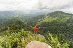 Freedom man with hands up in the rainforest mountains. Stock Images