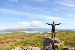 Freedom man in nature on iceland free. Freedom man in nature on iceland with arms enjoying free happiness in beautiful icelandic landscape Stock Image