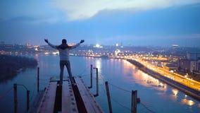 Freedom, man raising hands on top of bridge, enjoying amazing night view on city stock video footage