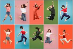Freedom in moving. Pretty young woman jumping against orange background stock image