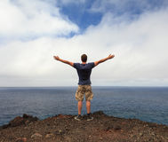 Freedom or nature lover concept. Man with arms raised at seashore stock image