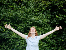 Freedom in Nature - Open Arms. Happy young woman stands in nature with arms open wide - an expression of freedom, joy or worship Stock Image