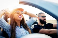 Freedom of the open road.Young Couple Driving Along Country Road In Open Top Car royalty free stock photos