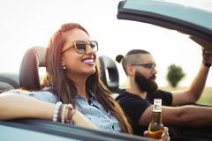 Freedom of the open road.Young Couple Driving Along Country Road In Open Top Car. stock photography
