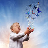 Freedom, peace and spirituality. Boy releasing butterflies into the air concept for freedom, peace and spirituality Stock Images