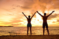 Freedom people living a free happy life at beach. Freedom people living a free, happy, carefree life at beach. Silhouettes of a couple at sunset arms raised up Royalty Free Stock Image