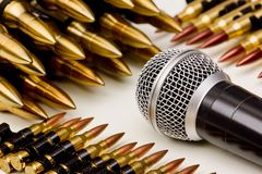Freedom of the press. Microphone vs. Bullets / Freedom of the press is at risk concept / World press freedom day concept royalty free stock photo