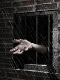 Freedom rain. A prisonier widens his hand through the narrow window of his jail, to receive the cool, fresh and benefactress rain