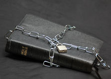 Freedom of Religion. A leather bound Holy Bible imprisoned by a chain and a lock. A freedom of religion concept royalty free stock images