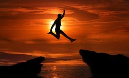Man jumping over precipice between two rocky mountains stock images