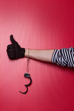 Freedom - robber hand with unlocked handcuffs on hand. Robber hand on red background Stock Images