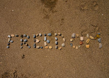 Freedom Sand. Freedom written with little rocks on the wet sand Stock Photography