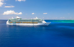 Freedom of the Seas giant cruise ship was tendered next to the shore. Over 4,000 guests went out to visit tropical island. Royalty Free Stock Image