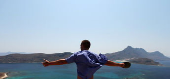 Freedom sensation of a man with arms open. A panoramic view from Gramvousa, Crete, Greece over the sea and islands nearby combining crystal clear water of Royalty Free Stock Image