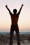 Freedom. Silhouette young man. With lifted hands upwards Stock Photo