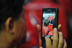 Freedom of Speach Rally. A protester uses a smartphone to photograph a red-shrit rally on the Royal Plaza on January 25, 2013 in Bangkok, Thailand. The red stock images