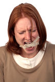 Freedom of Speech. A young woman tearing apart the tape over her mouth. A conceptual image about freedom of speech or censorship Stock Image
