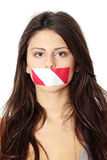 Freedom of speech. Concept. Young beautiful woman with red and white tape on her mouth. Isolated on white Stock Photos