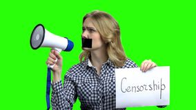 Freedom of speech and censorship concept. Caucasian woman protester with megaphone and tape over her mouth unable to speak out stock video footage