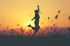 Freedom and suแcess - woman happy at meadow . Freedom and sucess - woman happy at meadow . Free cheering girl with arms raised enjoying serene sunset in stock photography