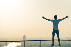 Freedom or success concept. White man standing at the edge of rooftop, stretching arms. Sunset on cityscape background Stock Images