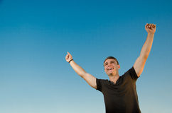 Freedom and Sunset version 1. Happy young men with hands raised and big smile against a clear blue sky Royalty Free Stock Photography