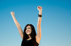 Freedom and Sunset version 2. Young, happy female with hands raised against a clear blue sky Stock Image