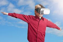 Freedom, technology and entertaiment concept. Small male child in red shirt wears VR glasses, studies possibilities of gadget, ima stock photos