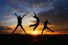 Freedom. Three friends jumping at sunset, freedom concept Stock Image