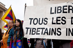 Freedom for Tibetans. Young tibetan girl holding a banner. Monk on the left. March 10th, 2012 Stock Photography